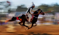 A Pakistani rider races to target a wooden peg during a tent pegging competition.