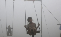 Children ride swings in a playground surrounded by smog in Lahore.