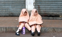 Girls in uniform sit on sidewalk while waiting for a school van in Karachi.