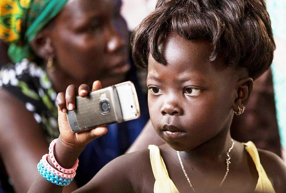 A little girl taking selfie with her mobile phone in Gambela, Ethiopia.