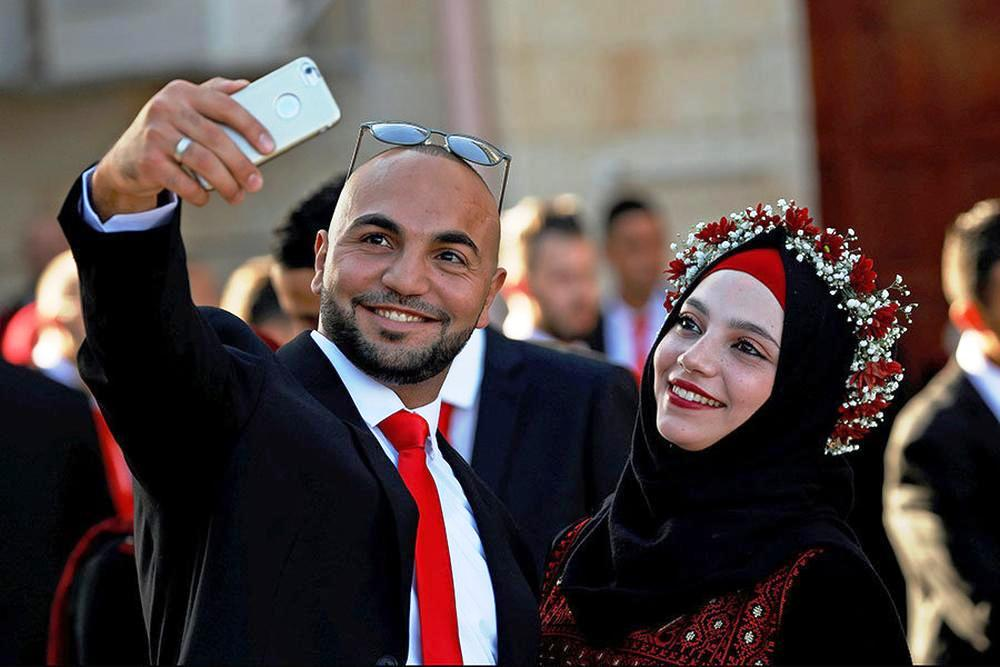 A Palestinian groom takes a selfie with his bride during a mass wedding in Ramallah, in the occupied West Bank