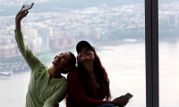 Two women take a selfie with a view of New Jersey from One World Observatory in New York.