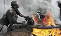 Man cooking cow skin to make the traditional Nigerian delicacy Kpomo