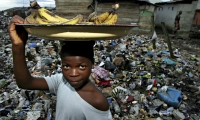 Child selling bananas by a dump