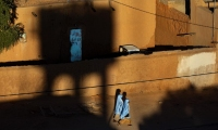 Two girls walking past a mud-walled building in Agadez.