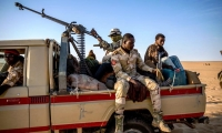 A young migrant, sits in the back of an army truck after being picked up by the military in the Tenere deser.