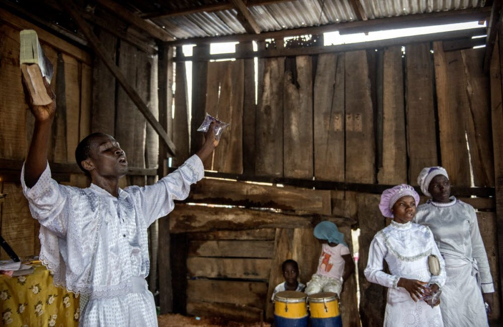 A Baptist minister holds a bible in one hand and a sachet of drinking water in the other during a Sunday service.