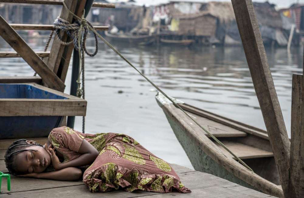A girl sleeps on a jetty in Makoko. There are some 100,000 inhabitants living in the slum.