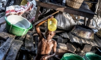 A young girl washing herself with a bucket bath. There is no running water in Makoko.