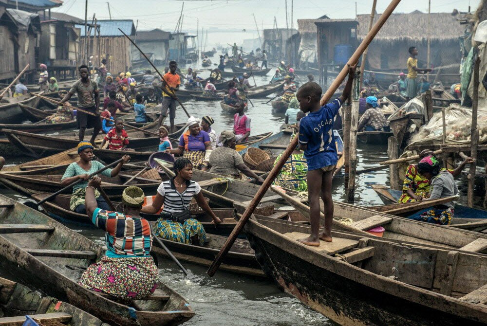 A child manoeuvres a canoe as rain falls in the Makoko slum. Which future for him?