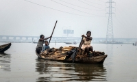 Two women paddle a canoe, loaded with firewood, back to Makoko.