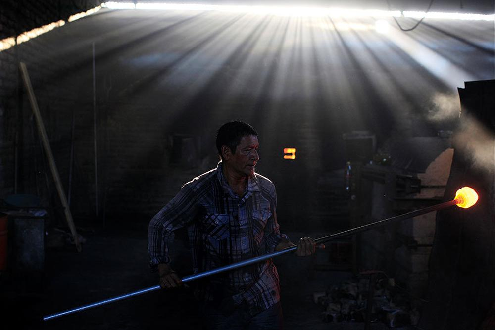 A glassmaker works next to a furnace at Cespedes factory in Olocuilta, El Salvador
