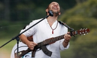 Colombian musician Cesar Lopez plays his guitar which he merged with a real weapon.
