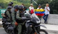 "Opposition supporters hold a national flag with the word ""Resistance"" written on it as they face members of the National Guard, in Caracas, Venezuela."