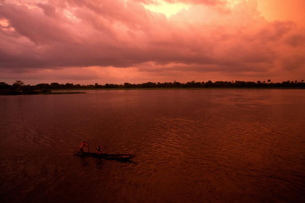 Two men paddle a pirogue (canoe) towards a boat travelling on the Congo River.