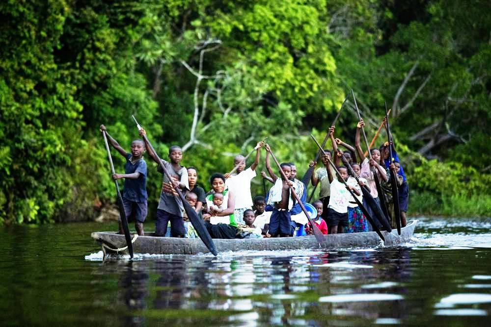 A man and his 18 children travelling by pirogue (canoe) on the Congo River to church for a Sunday service.