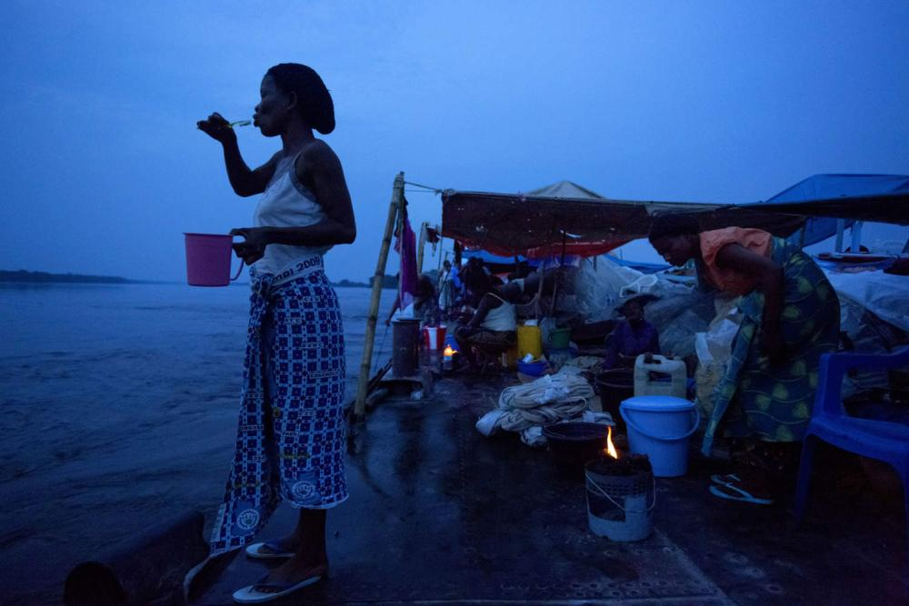 A woman brushes her teeth in the dawn light on the Congo River between Mbandaka and Lisala.