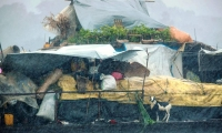 People and animals shelter during a heavy rain storm soaking a vessel on the Mongala River, a tributary of the Congo River.