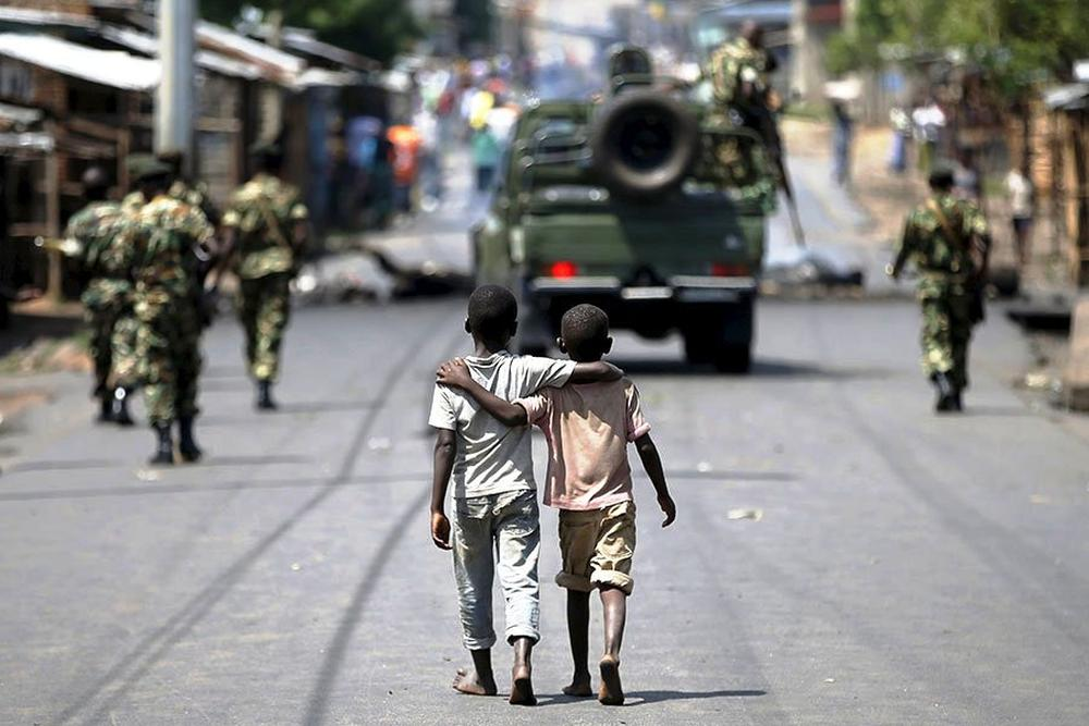 Boys walk behind patrolling soldiers in Bujumbura, Burundi.