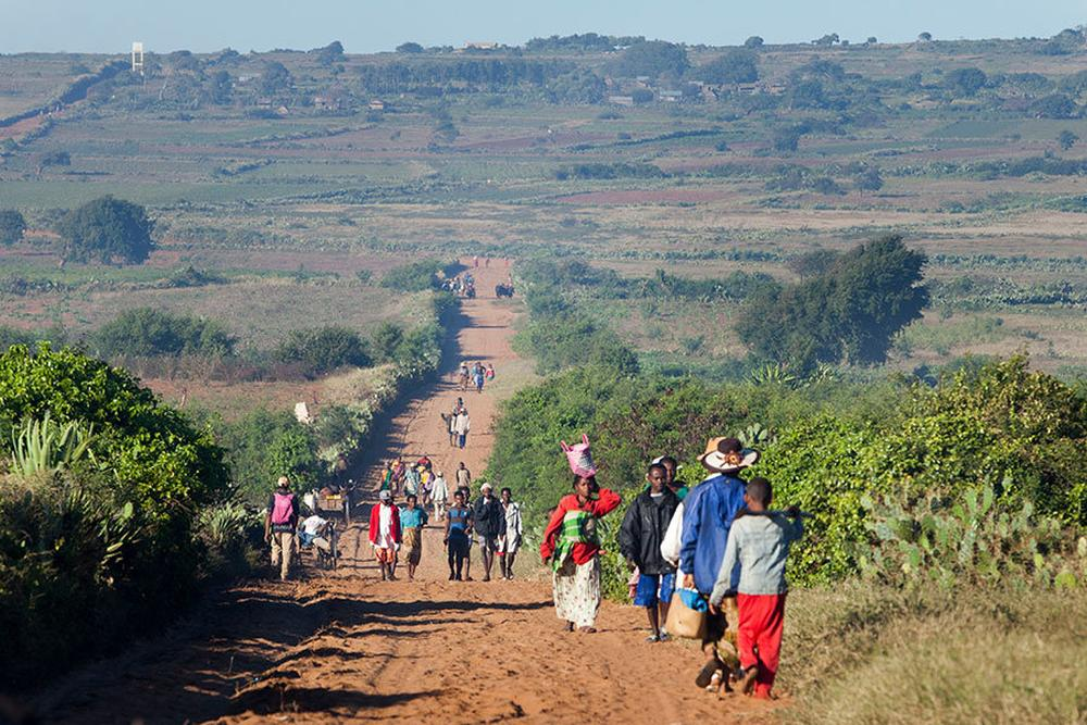 People walk down a dirt road outside Ambovombe, Madagascar.