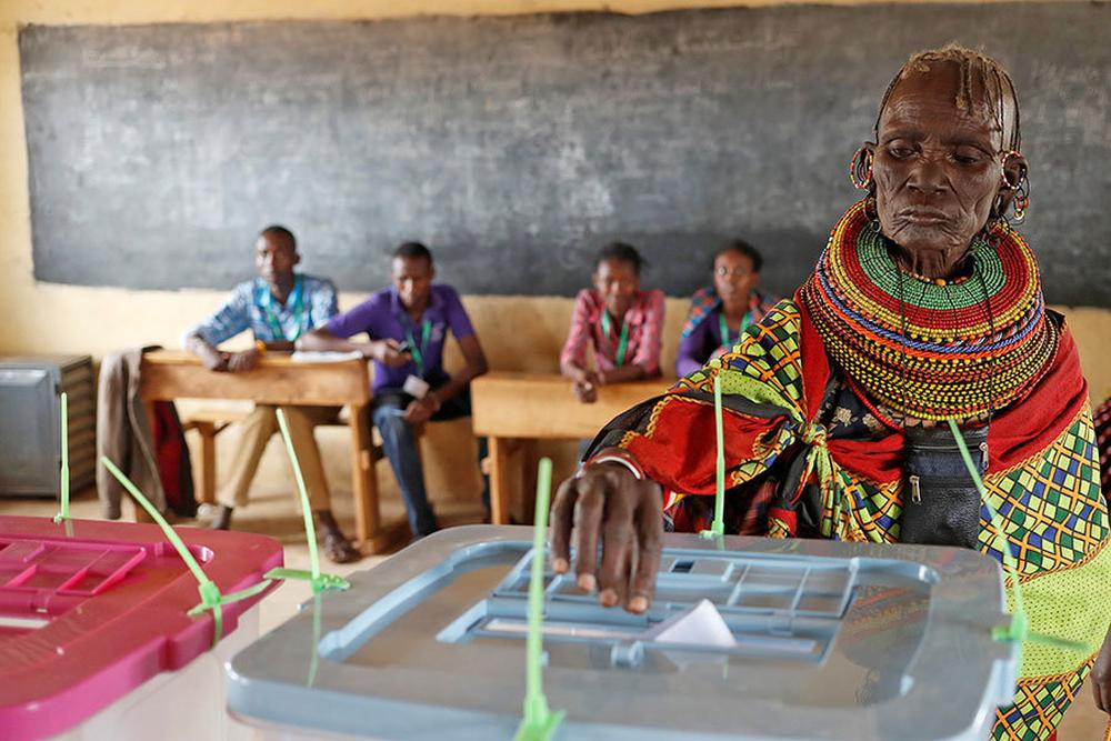 A Turkana tribeswoman casts her ballot at a polling station during the election in a village near Baragoy, Kenya