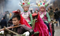 Children in traditional costumes are carried by villagers during a local celebration in Dong village, Guizhou province