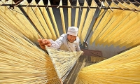 A villager hangs hand-made noodles up to dry in Linyi, Shandong province