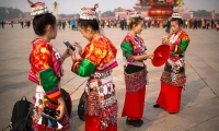 Women in ethnic minority dress look at their smartphones as they stand on Tiananmen Square in Beijing