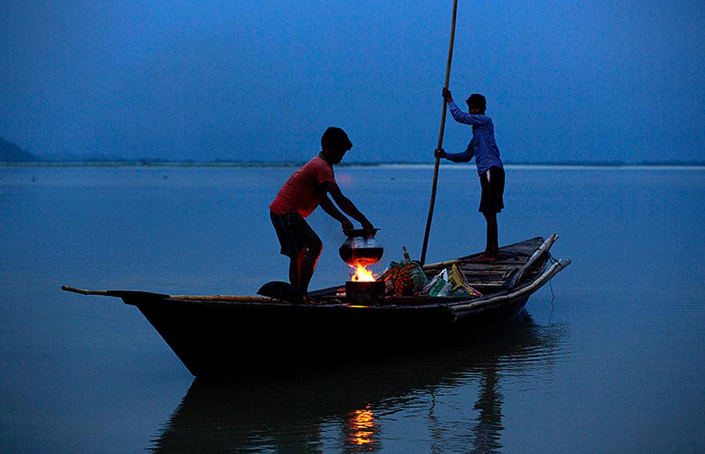 Fishermen prepare dinner before they go fishing in the river Brahmaputra in Guwahati, Assam state.