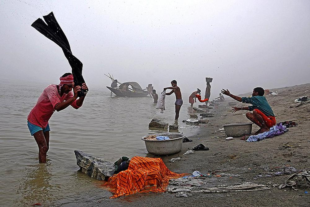People wash clothes on the banks of the river Brahmaputra on a foggy winter morning in Guwahati.