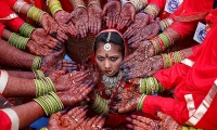 Brides display their hands decorated with henna around a bride during a mass marriage ceremony in Ahmedabad.