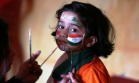 A school girl gets her face painted in the colours of India's national flag.