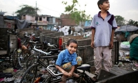 A young Indian boy reacts to camera sitting on a cycle rickshaw as children play in the evening at a slum in New Delhi.
