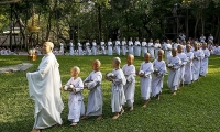 Thailand. A Buddhist nun walks in line with novice nuns to receive food from people during the Songkran Festival.