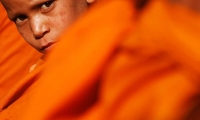 Nepal. A Buddhist monk waits for alms during the birth anniversary of Buddha at Boudhanath Stupa in Kathmandu.