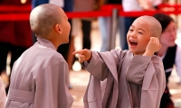 Two boys smiles after having their heads shaved.