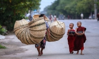 Myanmar. Two novice Buddhist monks walk alongside a basket seller to collect alms in Mandalay.