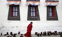 China. A Buddhist monk arrives for prayer session at Rongwo Monastery.