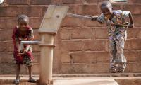 Little boy pumping water  for his sister. Some 2.2 billion people do not have access to clean water at home.
