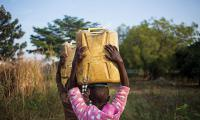 Uganda. Girls carry jerry cans to the wells to fetch water.