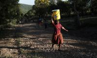 A girl on her way home with a bucket of water.